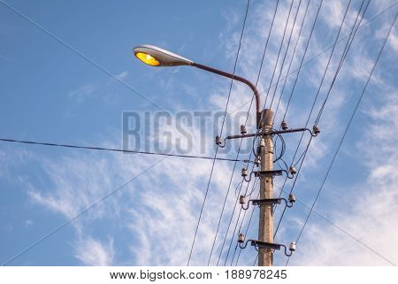 old electric pole with wires in a sunny day against the blue sky