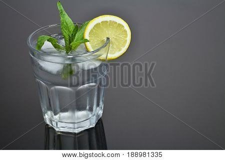 Refreshing glass of water with ice cubes flavored with lemon and mint. Summer refreshment. Fresh mint. Water in glass. Lemon and mint. Refreshing drink. Detoxification cure. Fresh water and forest mint.