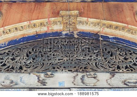 Wood carving and stucco ornaments decorating above the entrance door of the classic Sino-Portuguese architectural style shophouse building at Ban Singha Tha old historic area of Yasothon Province in the northeastern region of Thailand