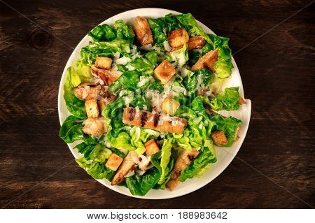 An overhead photo of a plate of chicken Caesar salad on a dark rustic background with a place for text