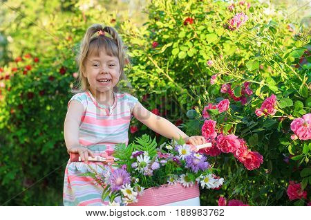Happy little girl riding a bicycle portrait photo. The child goes on a bicycle and carries a bouquet of flowers to the basket. A beautiful child is riding a bicycle in the garden.