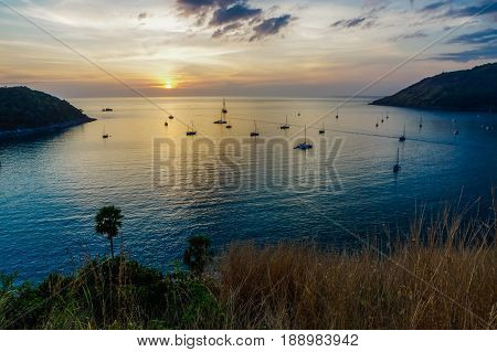 PHUKET, THAILAND - Naiharn bay with yatch boat at windmill viewpoint at sunset, Phuket Province in Thailand