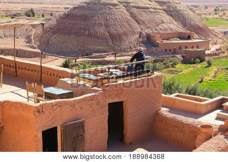 Ait Benhaddou Morocco - March 3 2016: Man sits on the rooftop cafe overlooking the valley in Ait Benhaddou Morocco Africa