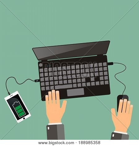 Top view. hands and laptop with connected smartphone.