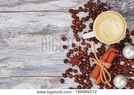 Latte and coffee grain on table. Cinnamon, badian, wooden background. Decoration with cup of coffe.