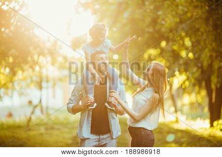 Happy Family Playing In Nature Late Afternoon Sunlight In The Fall, Summer. Mother, Father And Daugh
