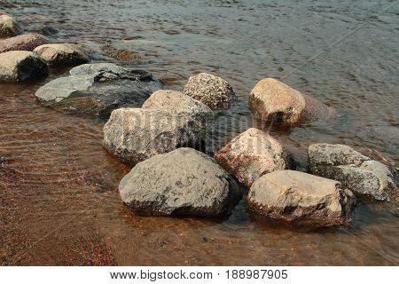 Round smooth boulders washed by waves close to