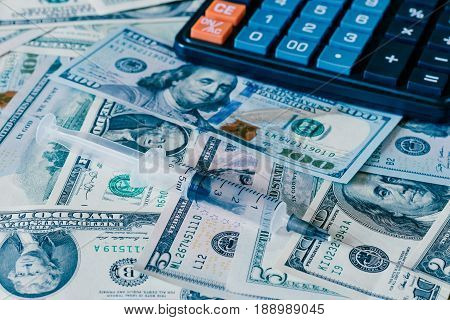 Hypodermic Needle With Dollars And Black Calculator.