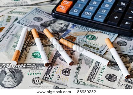 Cigaretes On A Dollars Background.