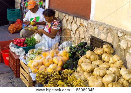 VALLADOLID MEXICO - FEBRUARY 11: Vendors selling fruit and vegetables in a street market in Valladolid Mexico on February 11 2017