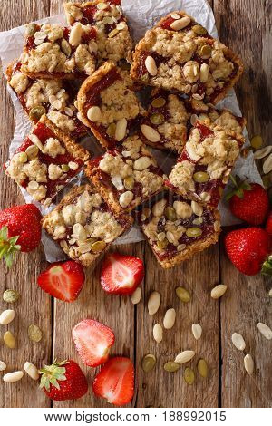 Tasty Strawberry Bars With Oatmeal And Nuts Close-up On The Table. Vertical Top View
