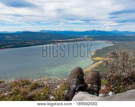 Hiking boots of Hiker resting in alpine tundra overlooking Little Atlin Lake near Tagish Yukon Territory Canada