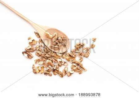 Peeled dried pieses of walnuts on wooden spoon isolated on white background