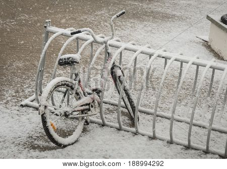 A Lonely Bicycle Covered With Fresh Snow Due To Weather Phenomena - Snowfall In Late April Near Mosc