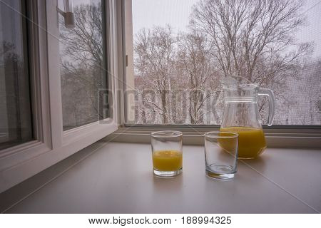 Scenic view of two glasses and a jug partially filled with orange juice on a sill and bare trees seen through the open window poster