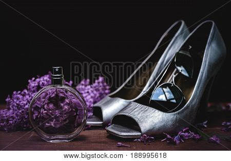 Female accessories. Silver shoes with perfume and sunglasses