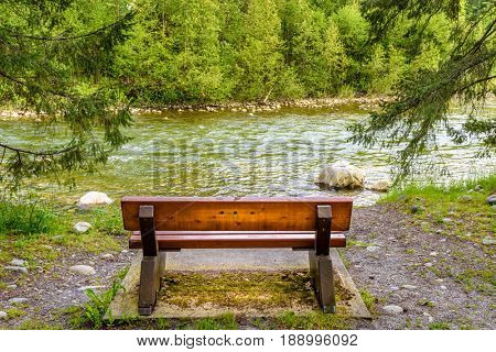 Beautiful Mountain River Trail with bench at the Capilano Park. North Vancouver, British Columbia, Canada.
