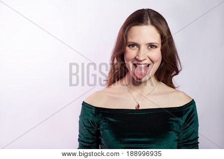 Portrait of funny crazy woman with freckles and classic green dress with tongue. studio shot on silver gray background.