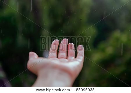 Close up Human hand under the spring or summer rain. Selective focus.