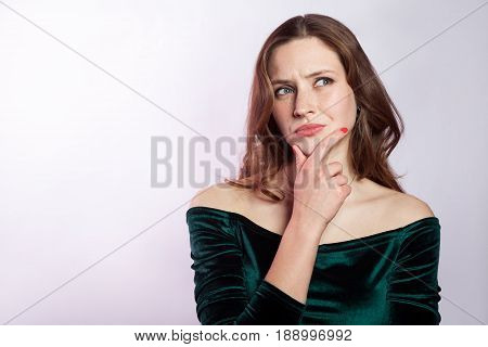 Portrait of thinkful woman with freckles and classic green dress. studio shot on silver gray background.
