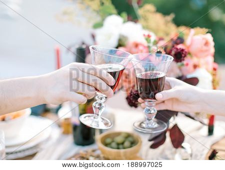 Close -up Of Couple Hands Toasting Red Wine on festively table with flowers and fresh food background. birthday, event, wedding concept. Man and woman drinking red wine.