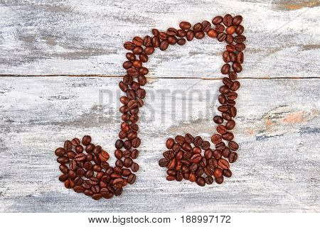 Melody shape from coffee beans. Music image on wooden background. Inspiration with coffee.