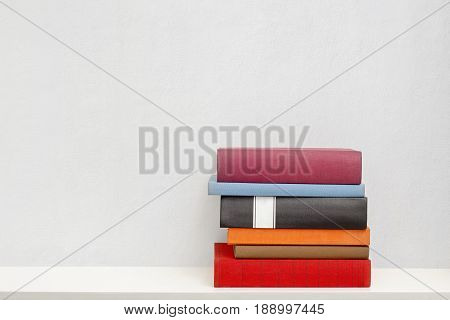stack of new colorful books in the white bookself