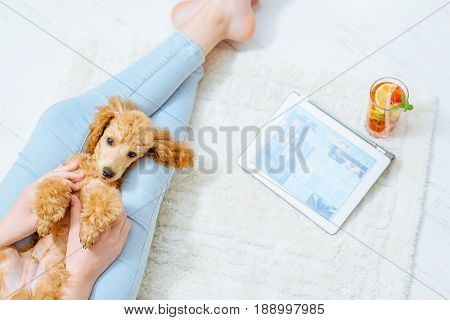 Young women is resting with a dog on the floor at home and using tablet .