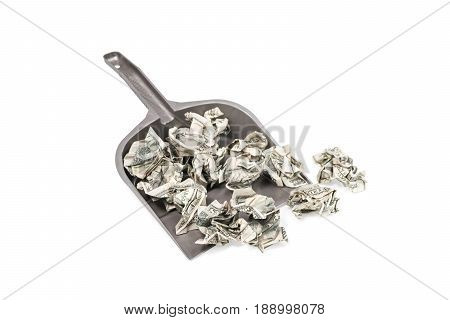 Pile of crumpled money in a garbage shovel isolated on white background