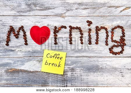 Note coffee break, wooden table. Red heart, word morning.