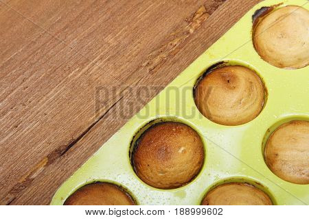 Sweet muffins on wooden background baked in silicone form. There is space for text placement.