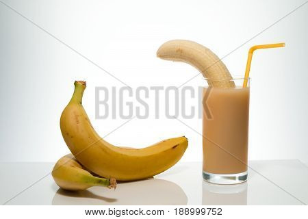 Healthy Food And Vitamins: A Cleared Ripe Yellow Banana In A Glass With Banana Juice With A Cocktail