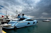 Fast and luxury yacht under a heavy cloudscape at marina Zeas Piraeus Greece poster