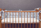 Vintage wooden empty baby cot with decorated pillows poster