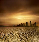 Global Warming and pollution theme with cracked land and the cityscape poster