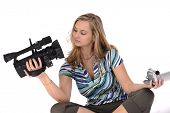 Young pretty woman with professional and amateur camcorders poster