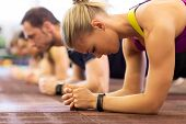 fitness, sport, exercising, people and healthy lifestyle concept - close up of woman with heart-rate tracker at group training doing plank exercise in gym poster
