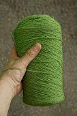 Hank of green woolen thread in hand poster