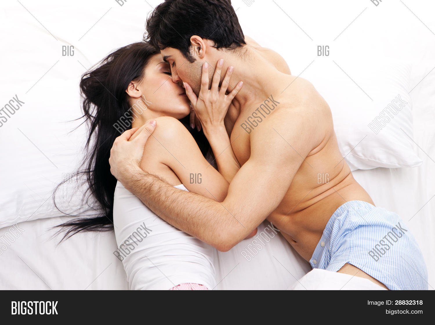 An Attractive Young Couple In A Loving Embrace Kissing One Another Bed