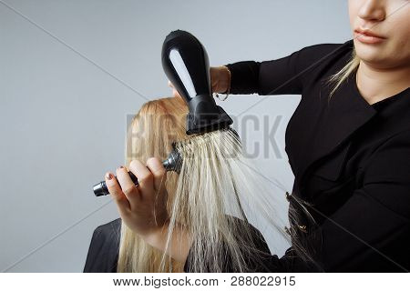 portrait of a girl Hairdresser dries hair with a hairdryer in beauty salon. girl dries hair blonde hair, winding them on a comb. dryer blows on hair. poster