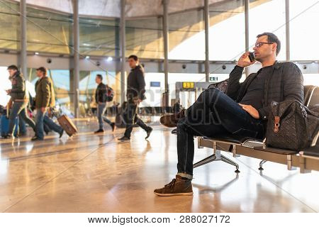 Male Traveler Talking On His Cell Phone While Waiting To Board A Plane At Departure Gates At Airport