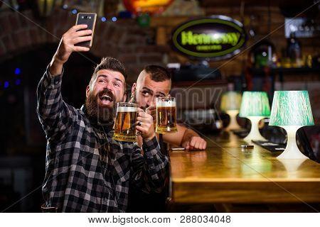 Send Selfie To Friends Social Networks. Man In Bar Drinking Beer. Online Communication. Man Bearded