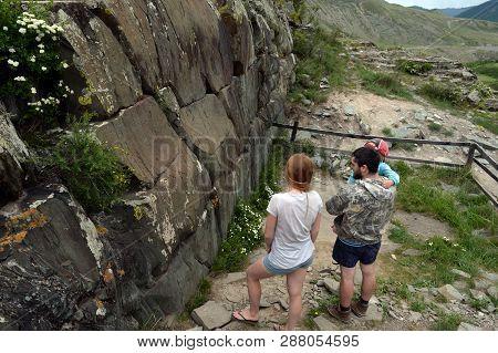 Altai Republic, Russia - June 8, 2018: Tourists View The Rock Petroglyphs In The Tract Kalbak-tash.