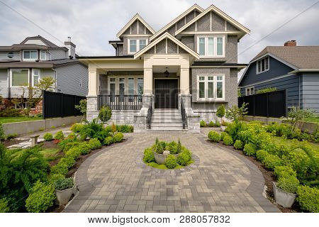 Main Entrance Of Residential House With Rounded Paved Pathway Over Front Yard On Cloudy Day. Luxury