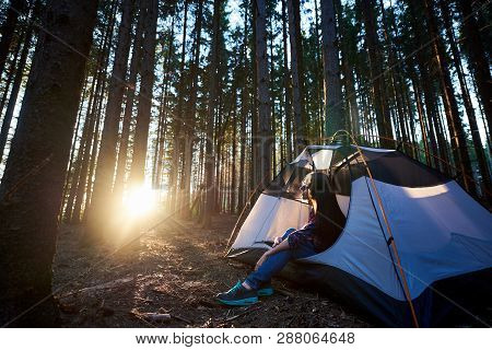 Evening Camping In The Forest. Happy Woman Traveller Sitting In White Tourist Tent, Enjoying Sunset.