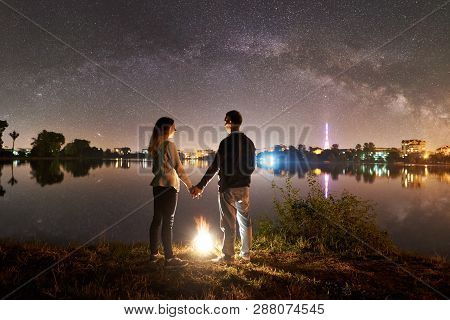 Back View Of Young Family - Man And Woman Standing On A Lake Shore Near Bonfire, Holding Hands, Enjo