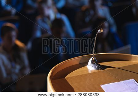 Close up of podium with speaker in auditorium