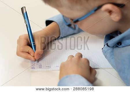 Hands Of A Boy Training In Writing. Writing Letters With A Pen In A Checkered Notebook.