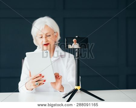 Senior Lady Blogger. Trendsetter Lifestyle. Elderly Woman With Tablet Making Video Tutorial.