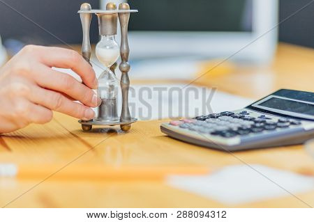 Close-up Of Hourglass In Front Of Businesspersons Hand Calculating Invoice Using Calculator.